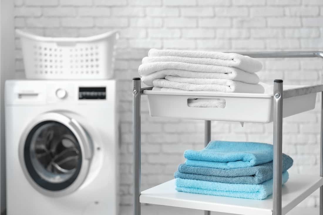Stack of clean towels on cart in laundromat. Paint Any Exposed Brick White