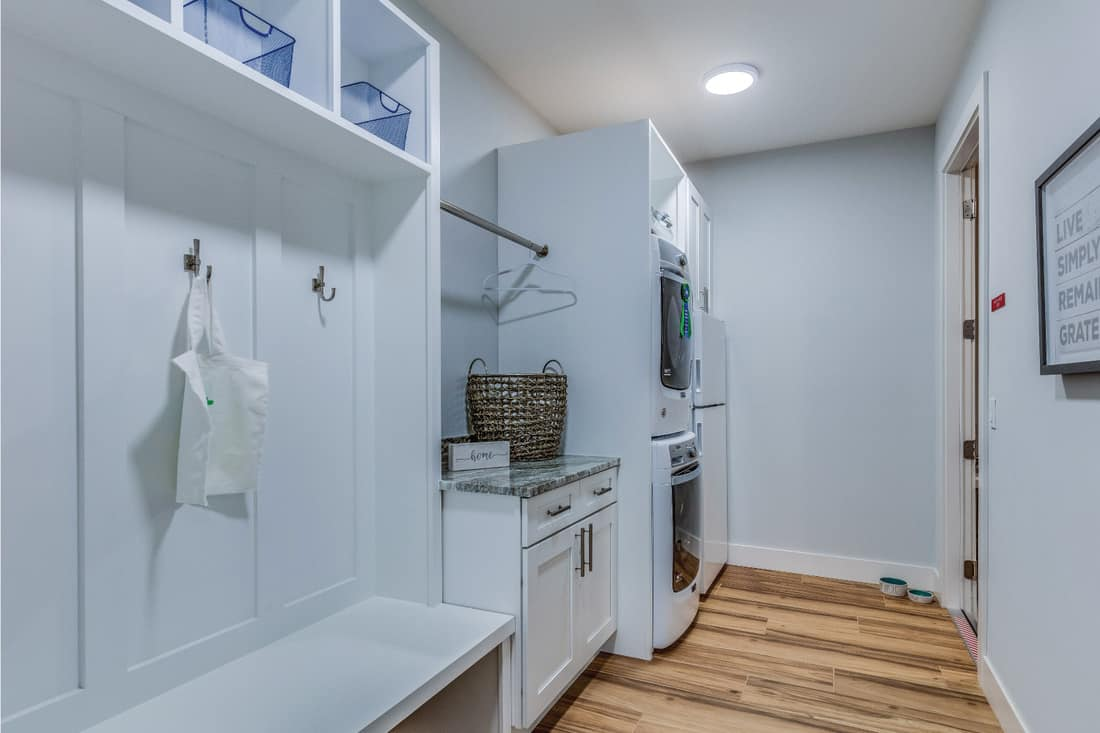 Stackable washer and dryer conveniently located next to mud bench, coat hooks and cubbyholes. Exceptional space design combining laundry room and mud room