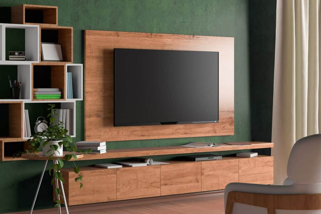 TV screen on the wall with wooden plate above the cabinet in modern living room with green wall, armchair, bookshelf, curtain, plant.