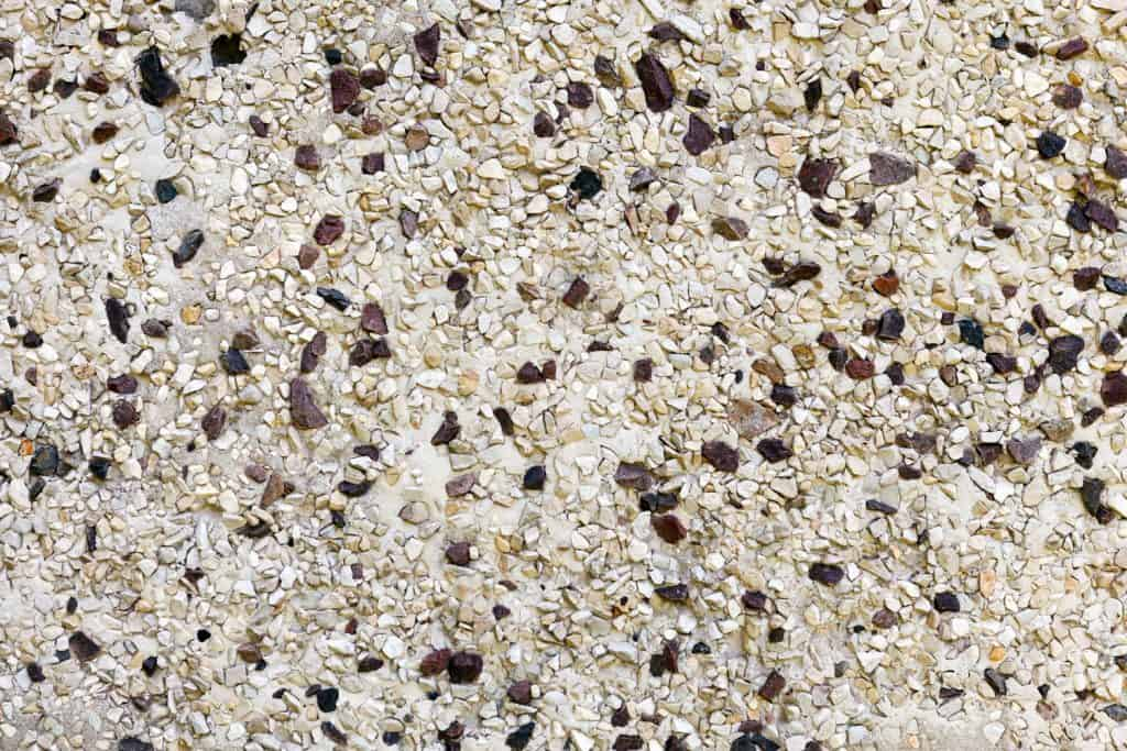 The wall is decorated with small natural marble and granite chips of white and brown color. Background image, texture