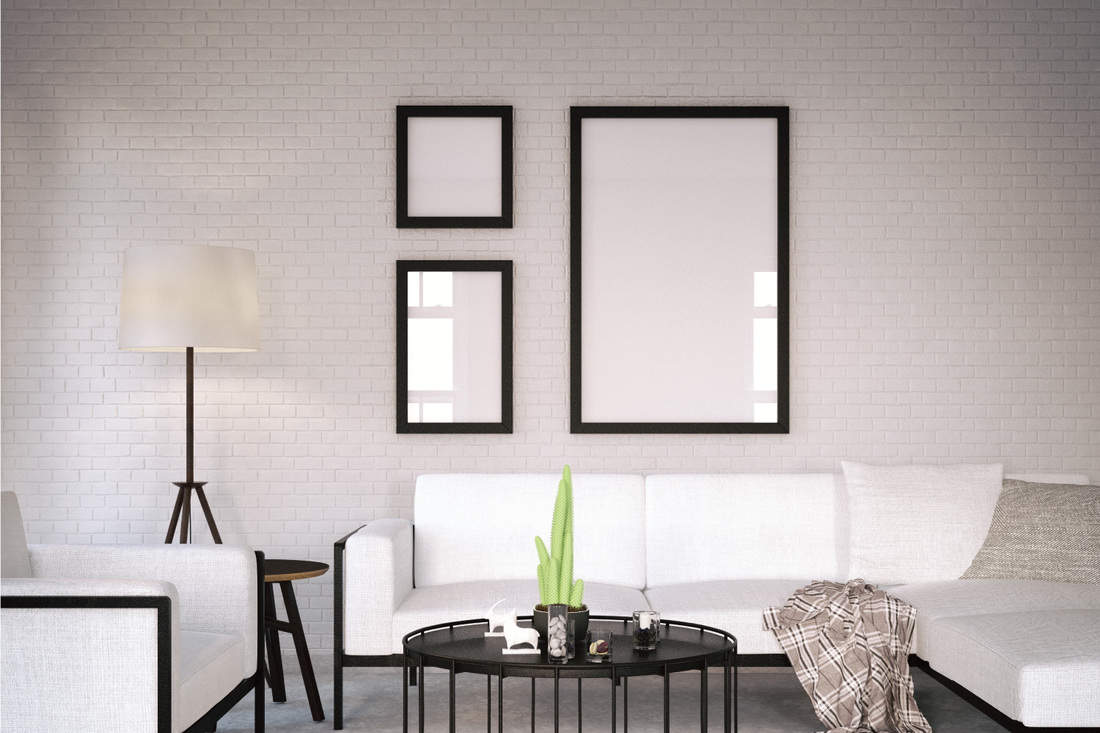 Three black picture frames in living room with white walls, sofa, floor lamp, and coffee table