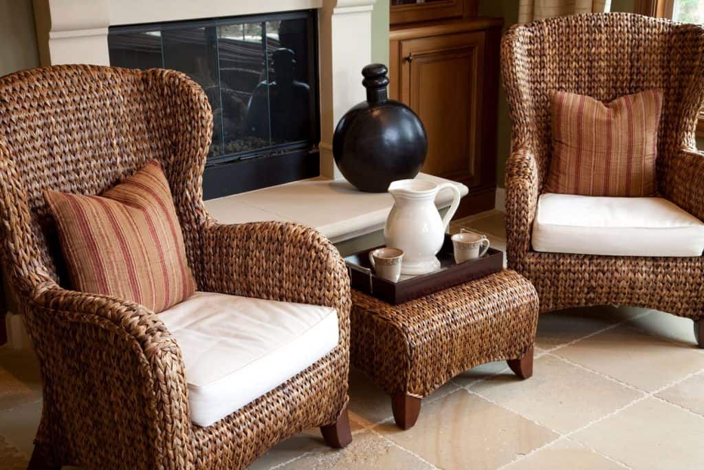 Two gorgeously made rattan accent chairs and a rattan end table on the middle