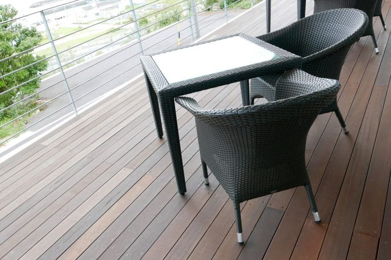 Two plastic outdoor dining chairs and table outside a wooden flooring patio, 6 Ways To Make Plastic Outdoor Furniture Look New