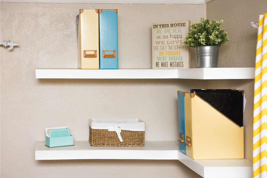Two white floating shelves simply decorated with yellow and blue. long corner shelves