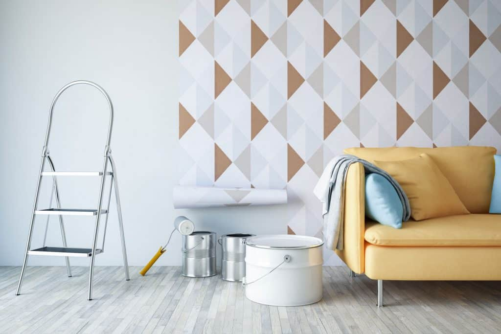 Unfinished patterned wallpaper inside a white and minimalist inspired living room with a yellow sofa