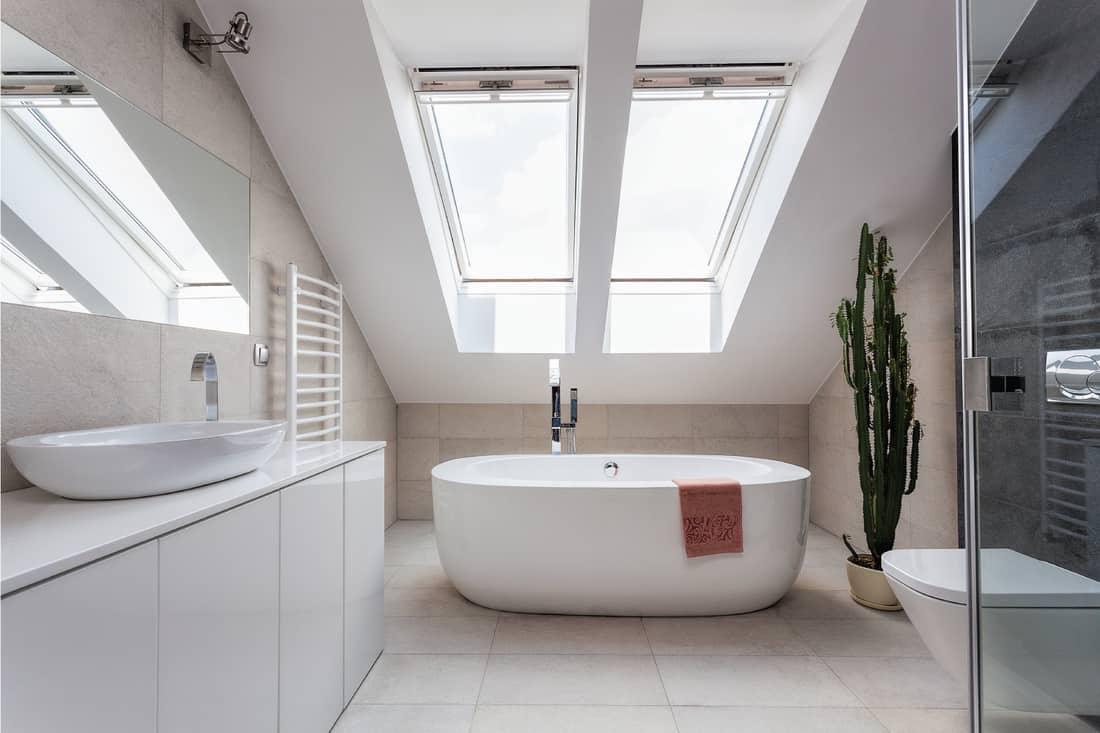 Urban apartment - white bathroom at the attic with bath tub