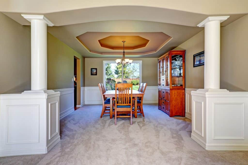 Vintage inspired dining area with cream painted walls, hardwood dining chairs, and tables, and a coffered ceiling