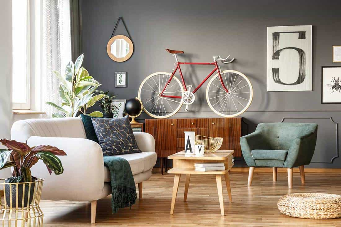 Vintage living room interior with good vibes, white comfortable sofa with cushions and blanket, green armchair, cupboard, small table, red bicycle and poster with number five on gray wall