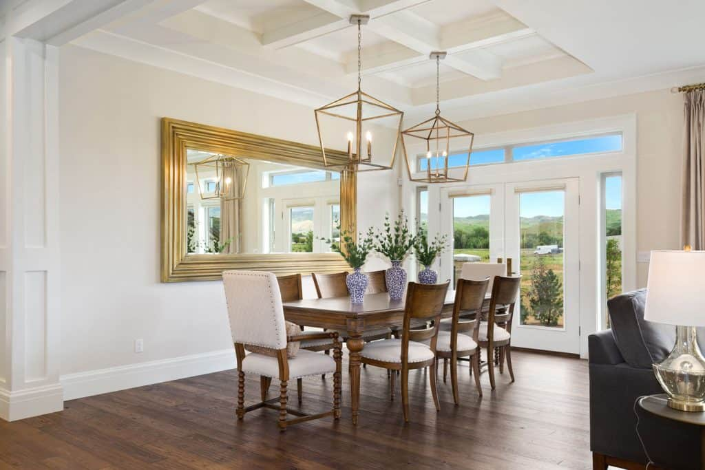 Vintage themed dining area with wooden chairs and flooring white painted walls and a white coffered ceiling