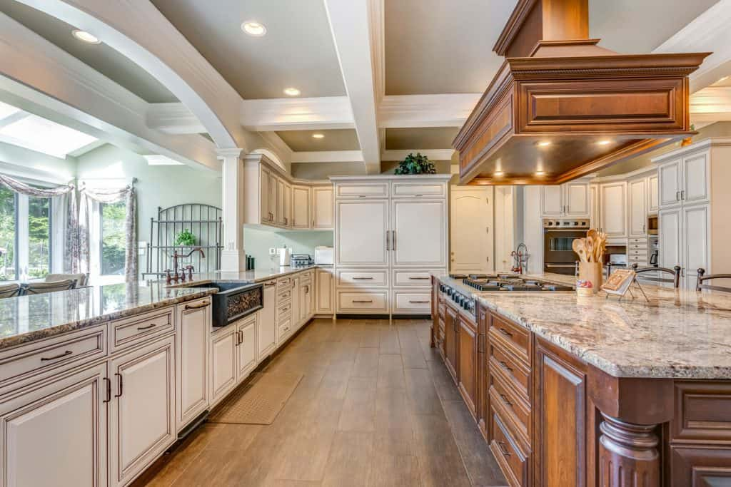 Vintage wooden designed kitchen area with white painted kitchen cabinetry and a hardwood kitchen breakfast bar