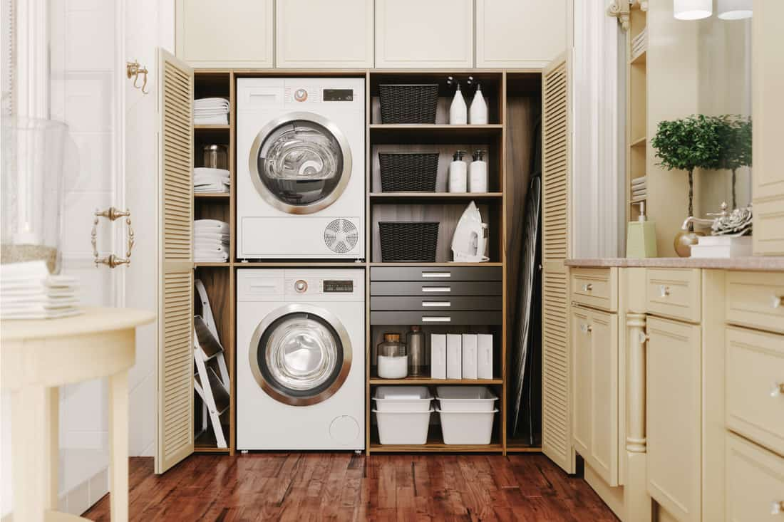 Washing machine and dryer in a luxury bathroom. classic with doors laundry room cabinet
