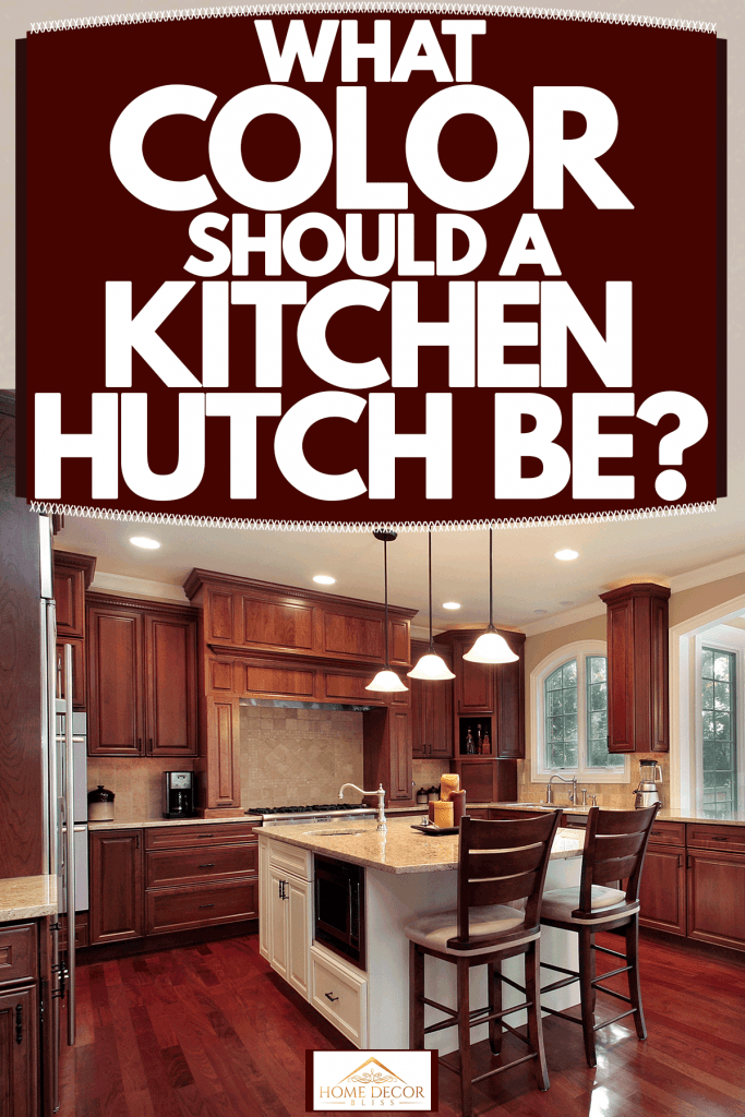 Interior of a rustic inspired kitchen room with hardwood flooring, dangling industrial themed lamps, and a bay window with a dining set near, What Color Should A Kitchen Hutch Be?