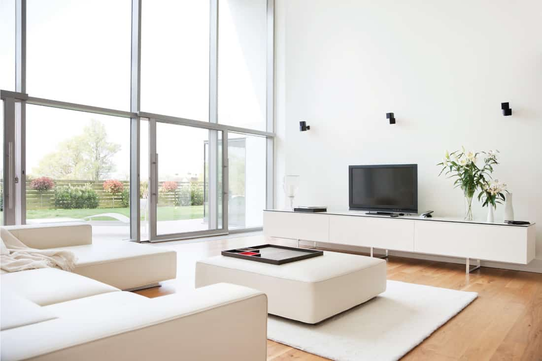 White and Modern. living room furnished with a modern sectional sofa, with a large white fabric coffee table
