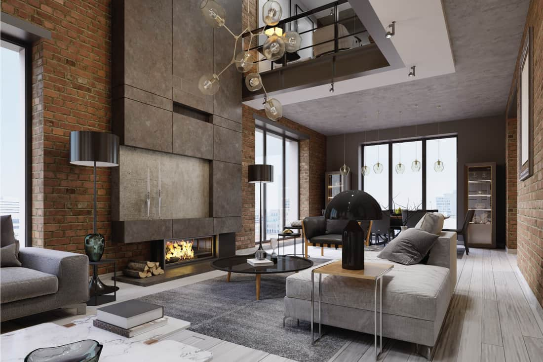 White and gray sofa and leather armchair with a magazine table and a large designer fireplace in a loft-style apartment with a living room and brick walls