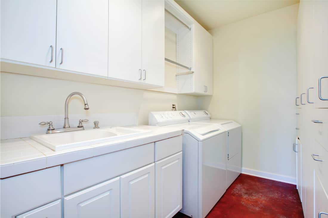White laundry room with a red floor and white wooden storage combination