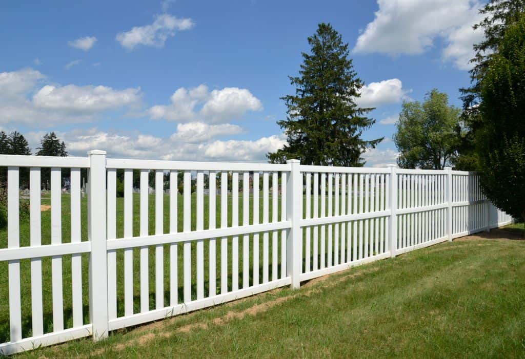White vinyl fence by green lawn