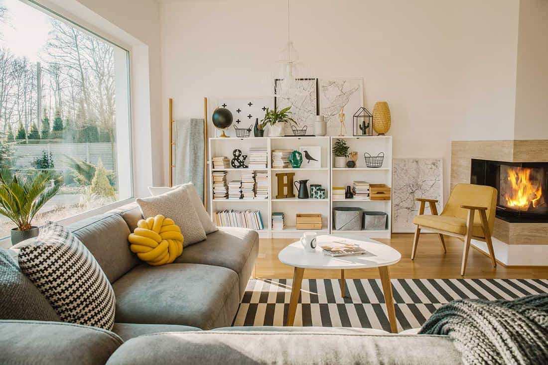 White wooden rack with books, decor, fresh plants and simple posters in bright Scandinavian living room interior with fireplace, coffee table and corner sofa