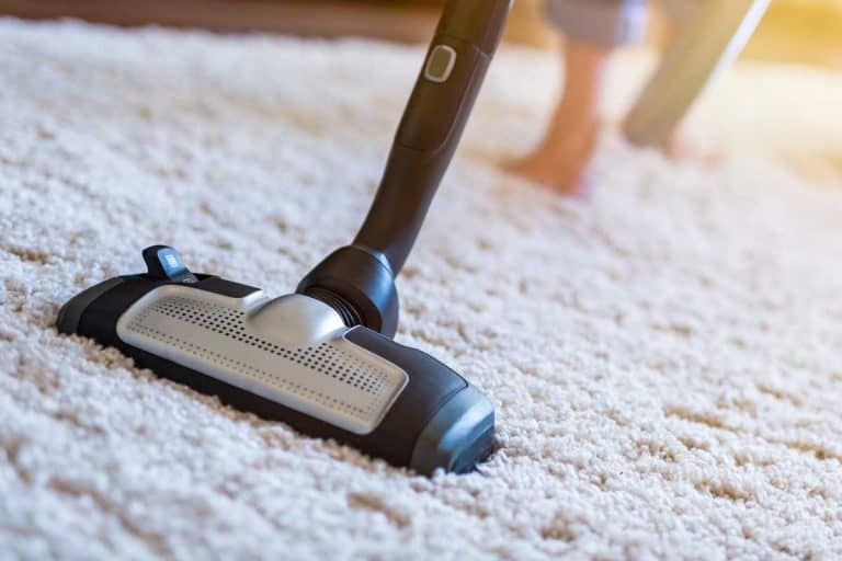 Woman using a vacuum cleaner while cleaning carpet in the house, How Do You Make Carpet Or A Rug Fluffy Again?