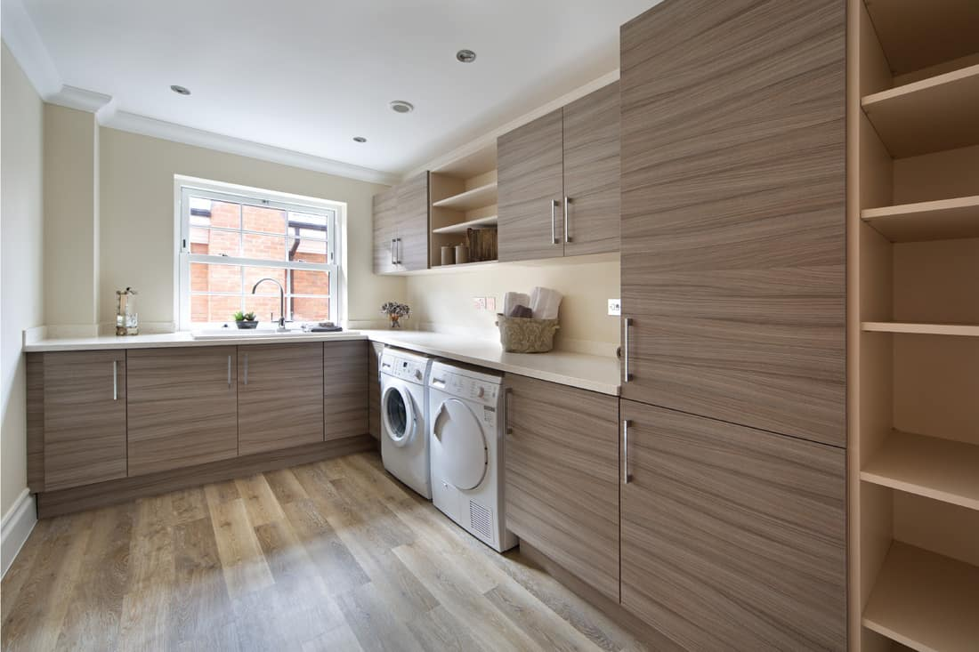 a lovely utility room in a large modern new home with ample cupboard space, work-top space and separate washing machine and dryer. vinyl design