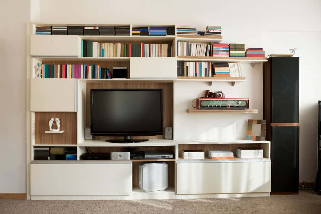 a wall unit in a livingroom with bookshelves and cupboard