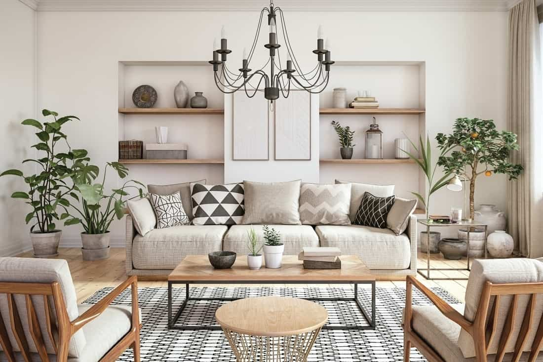 beige themed living room with simple chandelier lighting, open shelving, indoor plants on the corners and center table
