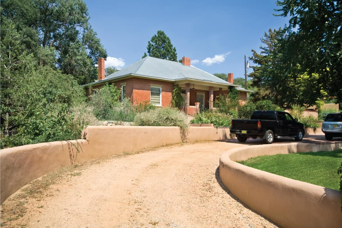 brick home with Gravel Drive Adobe Wall. Border Your Driveway With A Low Adobe Wall