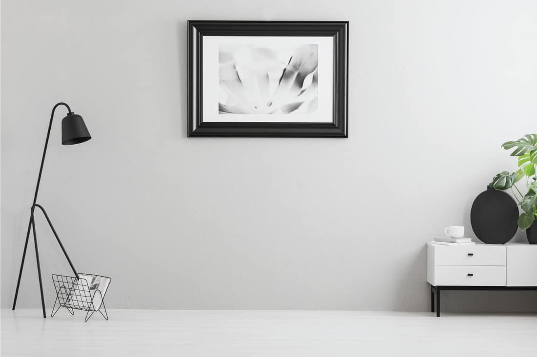 bright grey living room interior with simple poster in black frame, metal lamp, white cupboard and empty place for your couch