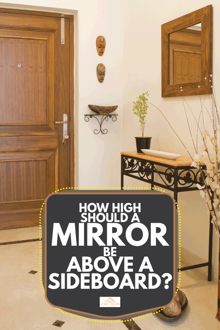 closed front door of a house with metal sideboard and mirror above it. How High Should A Mirror Be Above A Sideboard