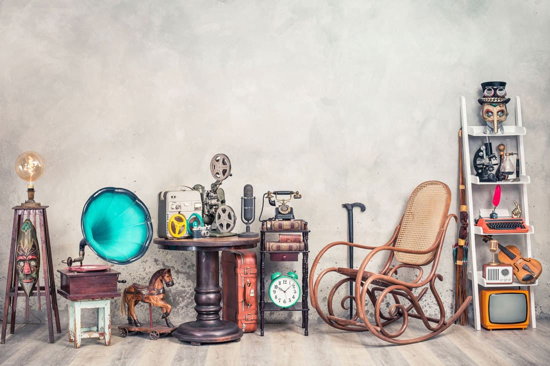 eddy Bear toy on chair, typewriter, vintage gramophone, old books, radio, globe, binoculars, carnival mask, camera, fiddle on shelf, steering wheel, plane, travel backpack, bow and other furniture used items, Where And How To Sell Secondhand Furniture