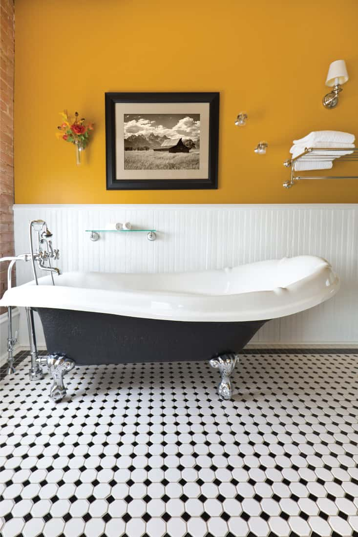 exposed brick wall and a window, a claw foot bath tub and black and white tile pattern on the floor, bold sunflower yellow painted wall
