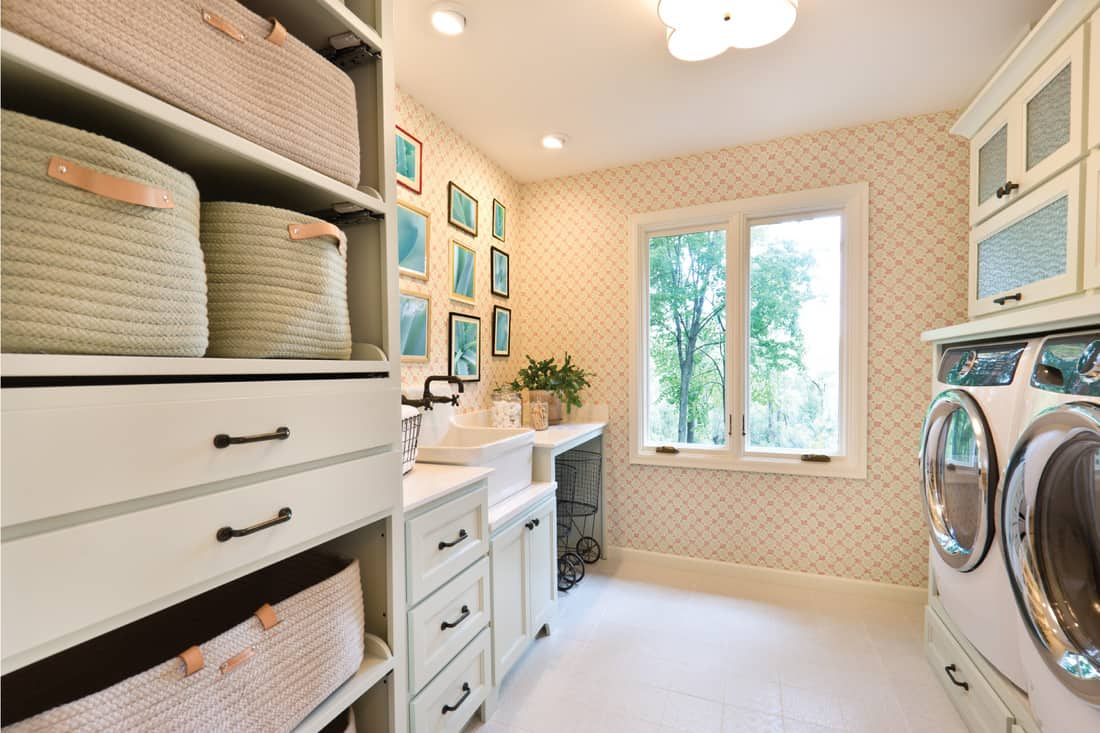 interior design of a utility laundry room in a residential home. with utility sink and fixture, washer and dryer, storage area. dainty off white