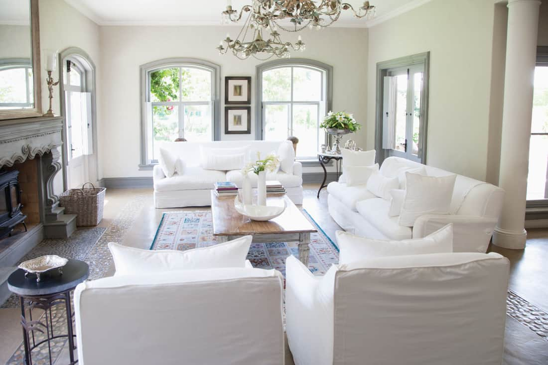 larger living room that is fully furnished with two sofas and two overstuffed chairs. Classic White Living Room With Gray Accents