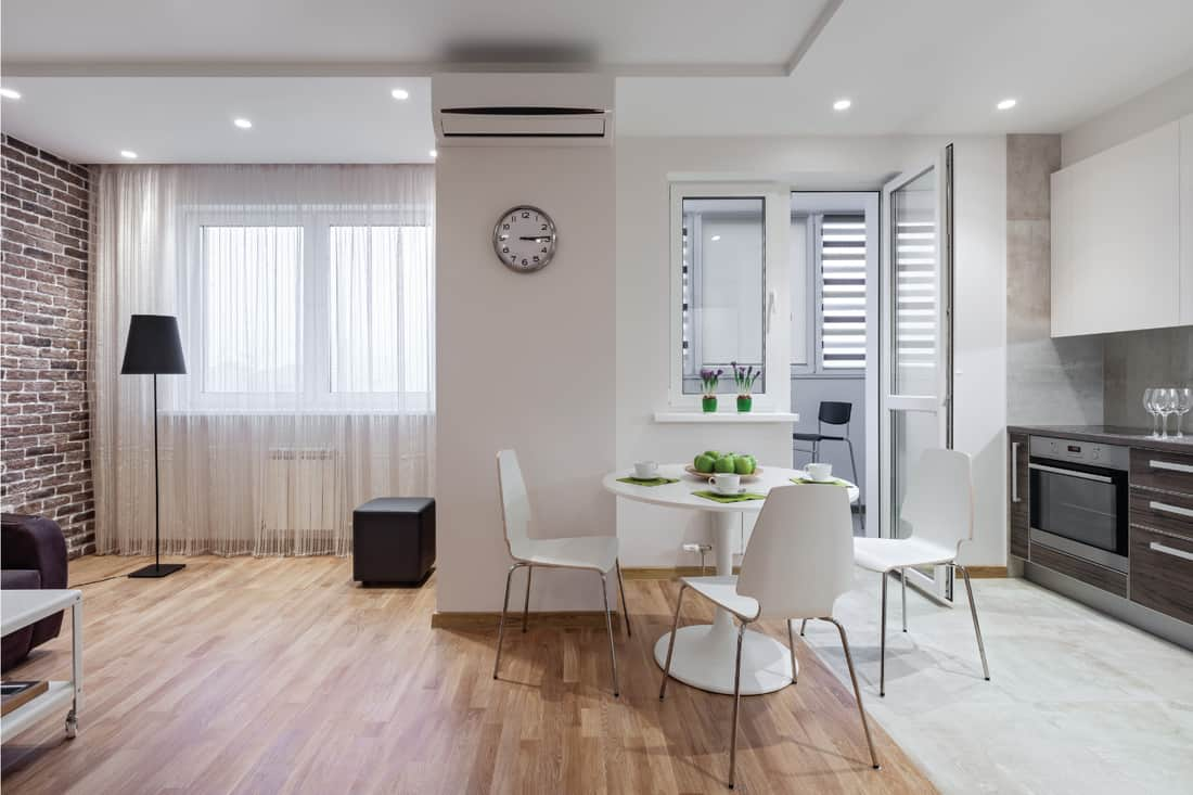 light colored floorboard and light gray flooring, black and white furnishings, brick wall and sheer curtains. smooth transition