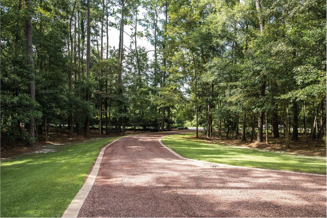 long red gravel driveway to a custom home with trees lining the driveway. Add A Cement Border To Your Gravel Driveway