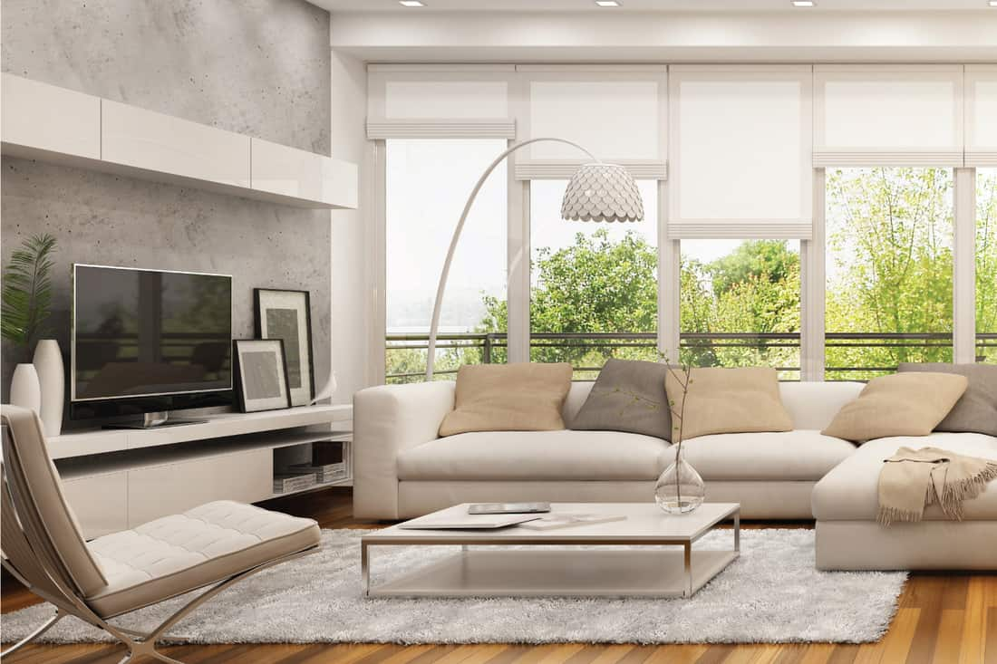 modern living room with large white sofa, flat screen TV, rug, center table