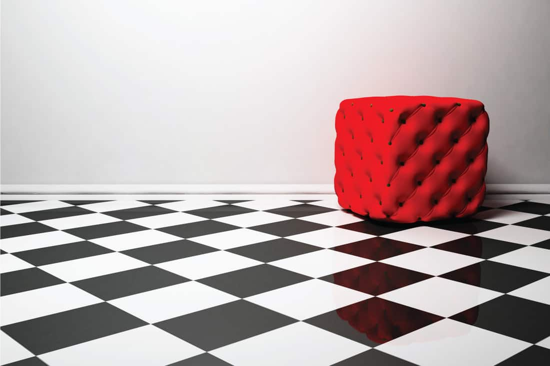 red pouf on the black and white floor with soft gray colored wall