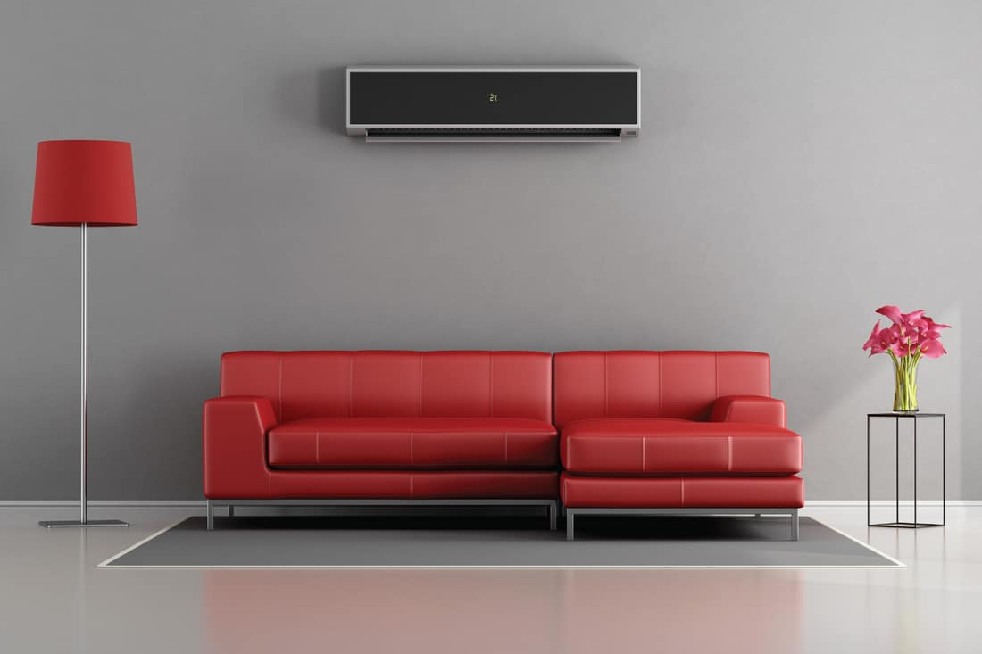 red sofa, red floor lamp, in front of a gray wall with inverter airconditioner