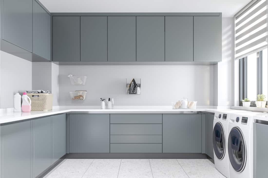 sleek blue and gray cabinets in a Laundry Room with washer and dryer