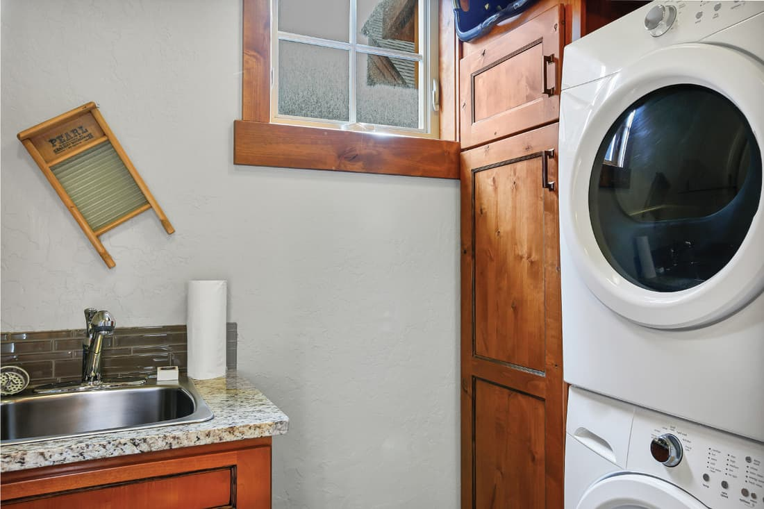 small Laundry room with stacked washer and dryer next to dark wood cabinets and a sink