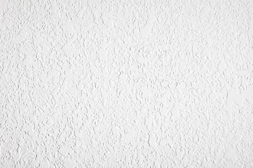 textured white plaster wall lit with high contrast light for more exaggerated texture and background