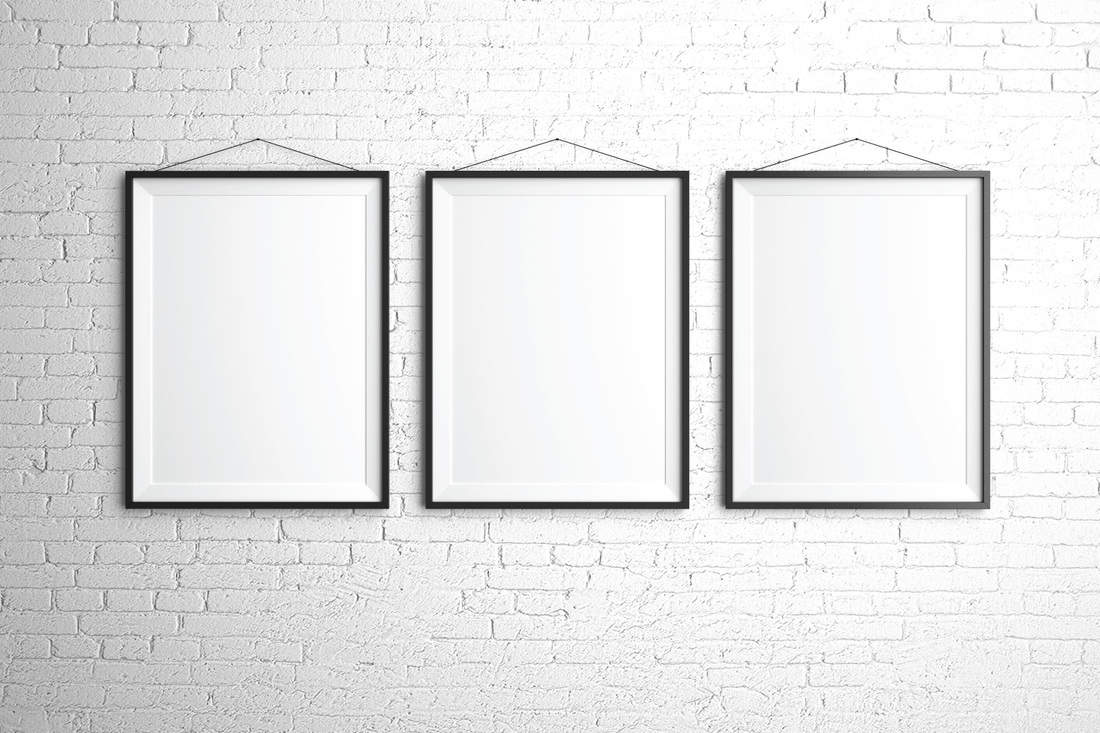 three frames hung on a white brick wall uniformly
