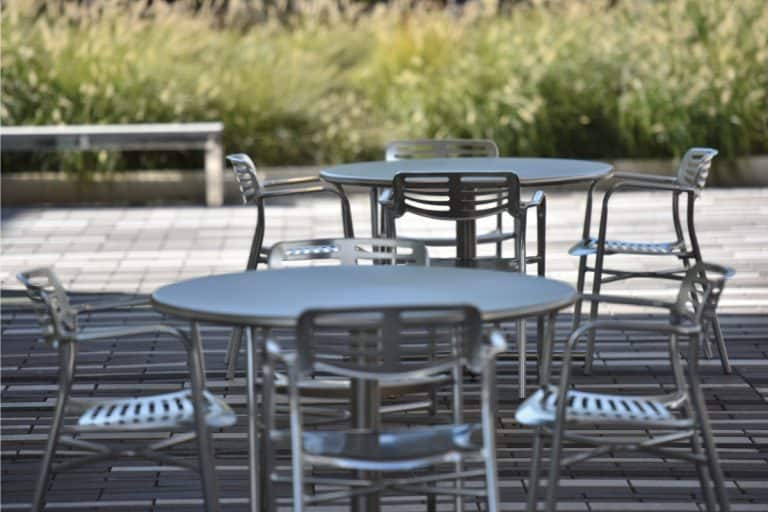 unoccupied outdoor aluminum tables and chairs under the shade. Does Aluminum Outdoor Furniture Rust