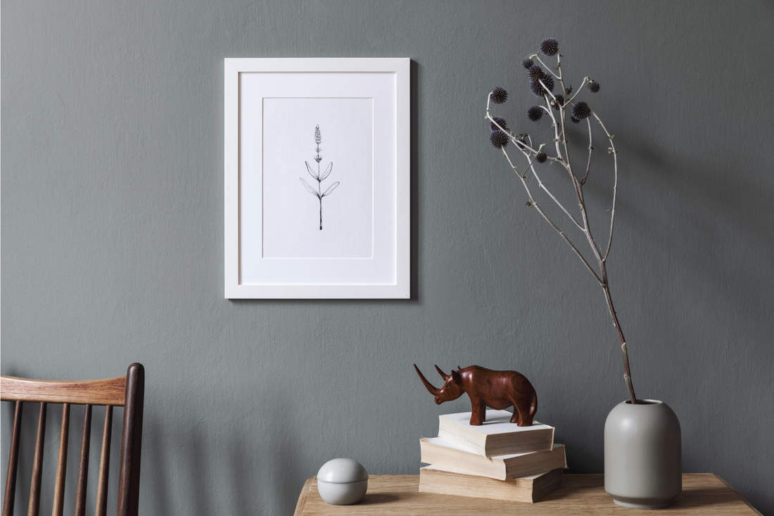 white framed photograph hanging on a gray wall, wooden furniture, stack of books