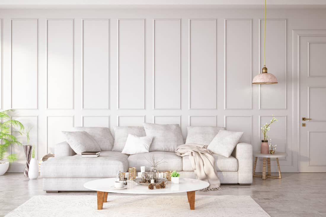 white paneled room. living room with white sofa and throw pillows, indoor plants, white wall panels
