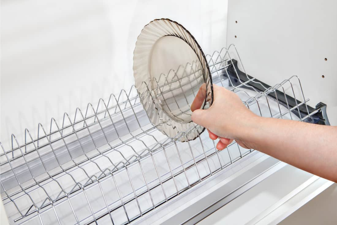 woman hand takes dish from inside wire plate drainer. wire shelves for dinner