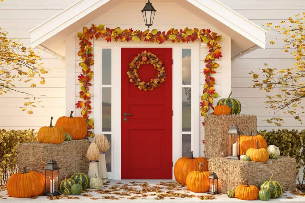 A Halloween themed front porch with maple leaves and pumpkins displayed at the door step