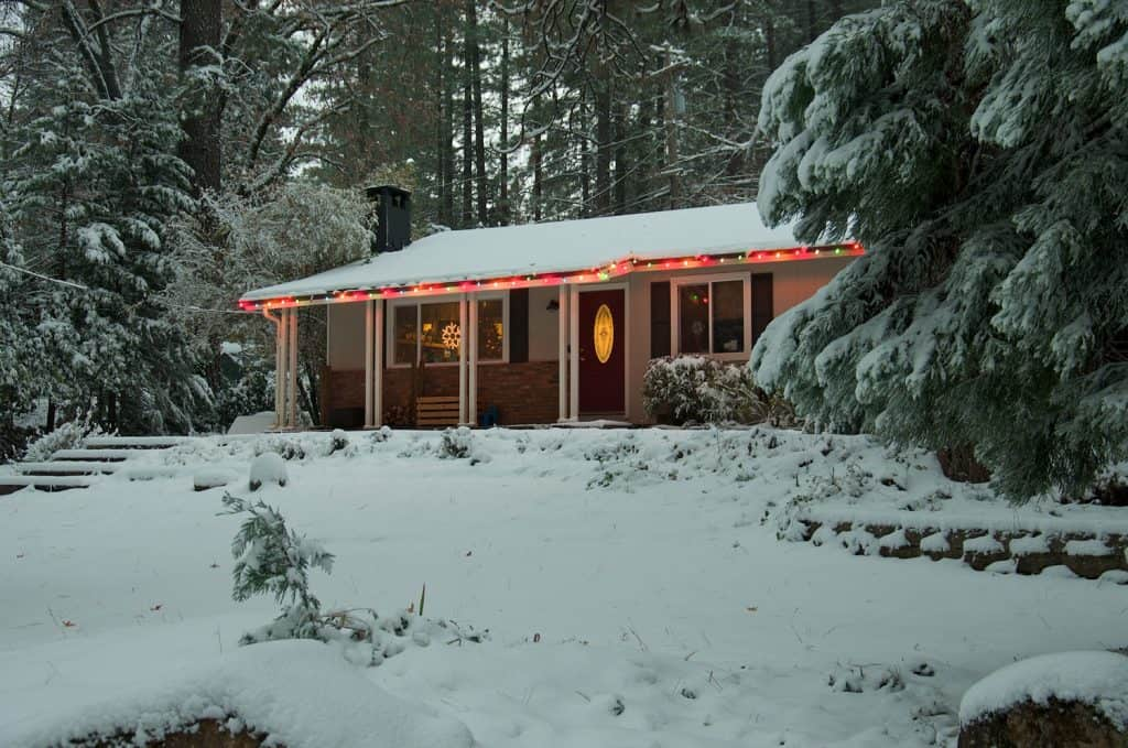 A Ranch style house covered in snow decorated with Christmas lights.