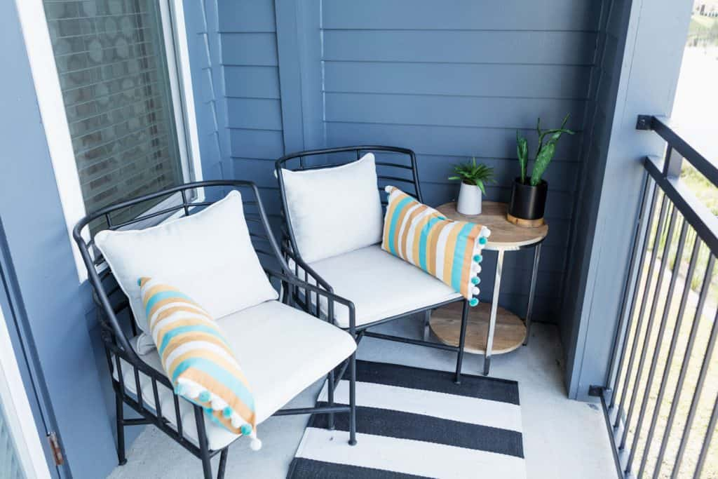 A blue colored porch with metal framed porch chairs with pillows and an end table on the side