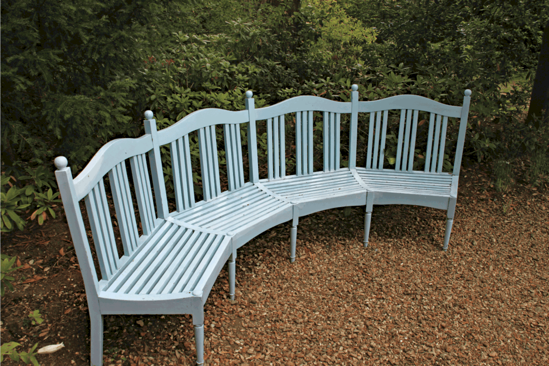 A blue curved bench in a shady area of a garden
