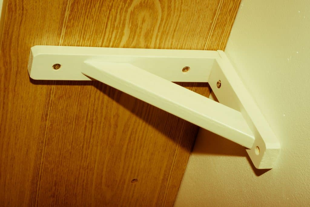 A bracket for wall mounting bookcases or dividers